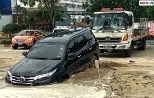 Terjebak Dalam Genangan Air, Mobil Ini Susah Dikeluarkan